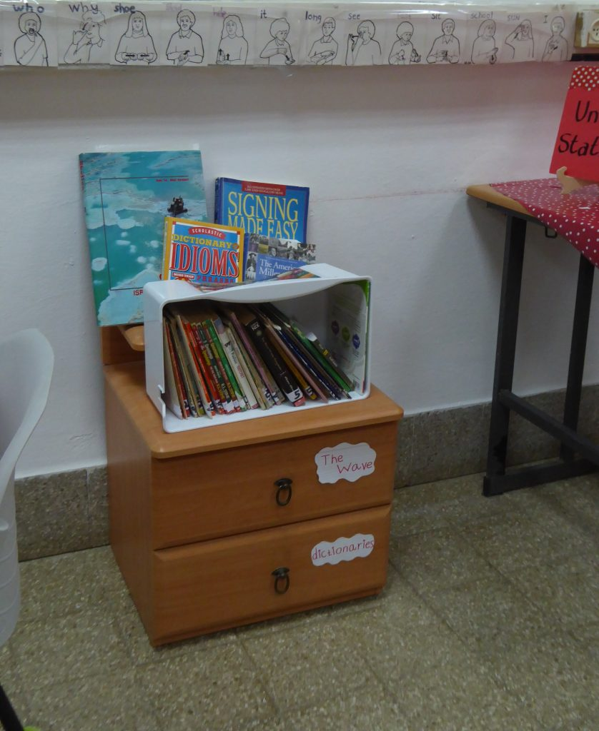 A corner of the classroom, with sign language translation cards, and a stack of books about sign language, idioms, and other classroom resources.
