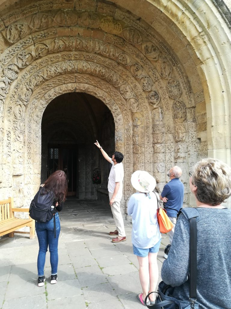 A tour guide showing some people a large, grand stone door of a building.