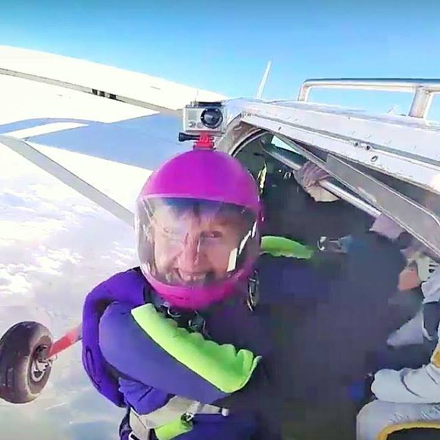 A woman jumping out of a plane to go skydiving.