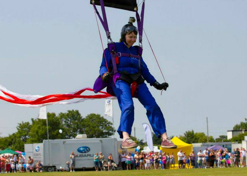 A woman coming into land a skydive at a show with spectators in the background.