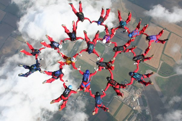 A group of over 20 skydivers holding hands in a circle formation above the clouds.