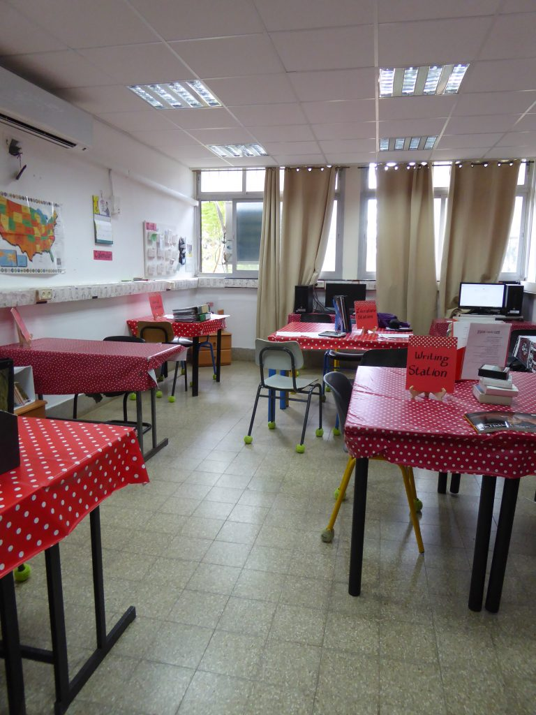 A classroom showing a writing station and literature station on different tables. The chairs have tennis balls on the feet so that there is less noise distraction when the classroom is in use.