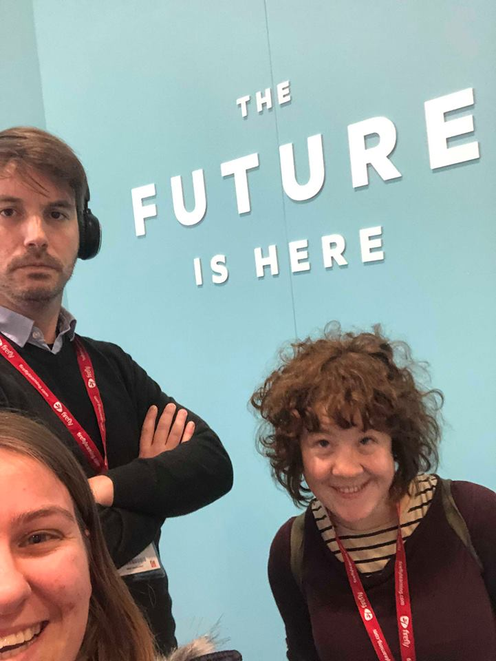 A selfie of Matt, Rosie and Jaz stood infront of a wall which says 'The Future is Here.'