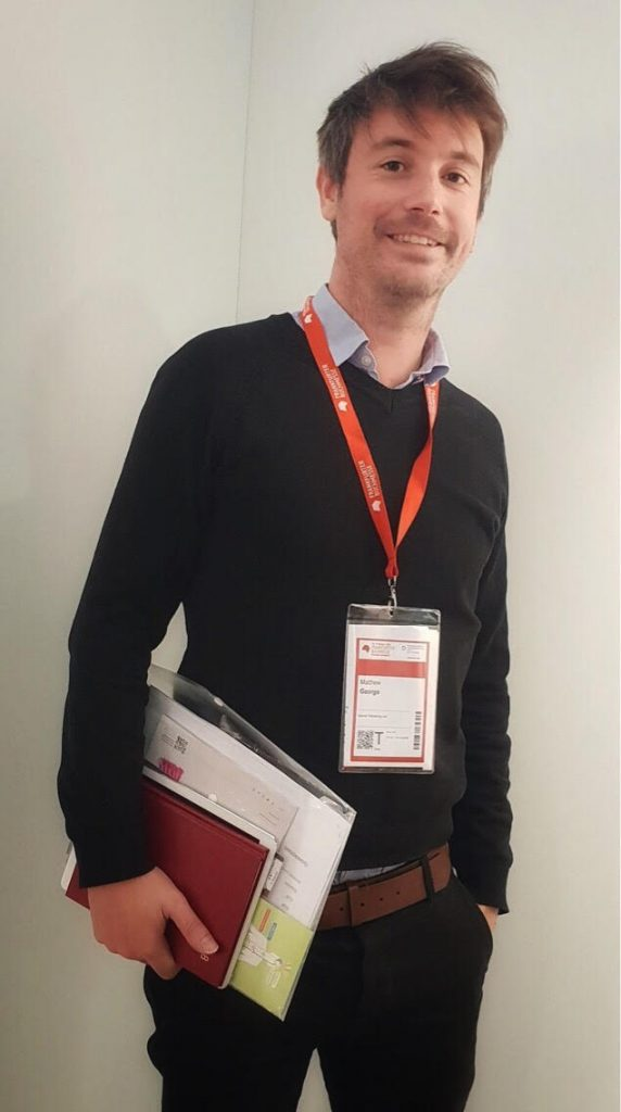 Matt, a tall, smiling man, wearing a conference lanyard, and holding papers and folders ready to go to a meeting.