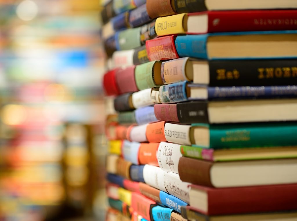Close up of an infinite stack of colourful books in a library.