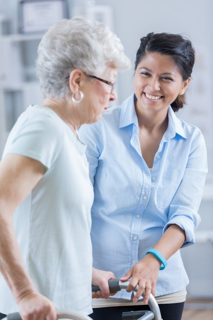 A friendly young woman assisting an elderly woman learning walking with a walking frame.