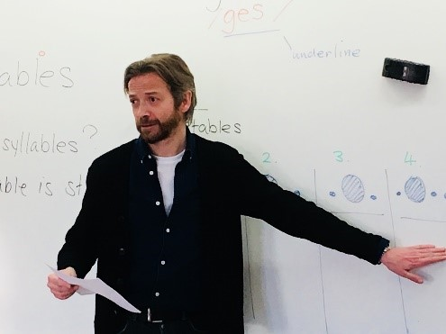 Photo of Mark McKinnon standing in front of a whiteboard.