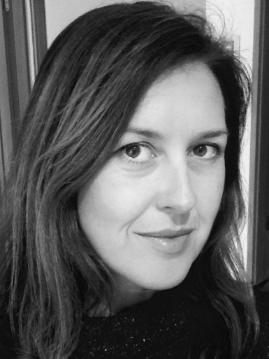 Black and white photo of Nicola Meldrum, a friendly looking woman with brunette hair.