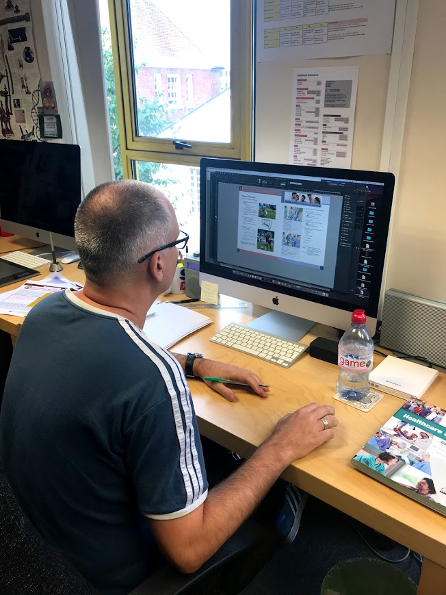 A middle aged man making changes to Coursebook using InDesign