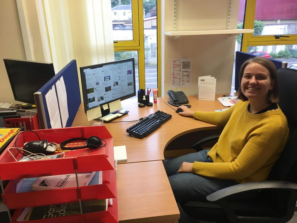 Jaz, a young woman with short brown hair and a mustard yellow jumper, sitting at her desk and smiling at the camera.