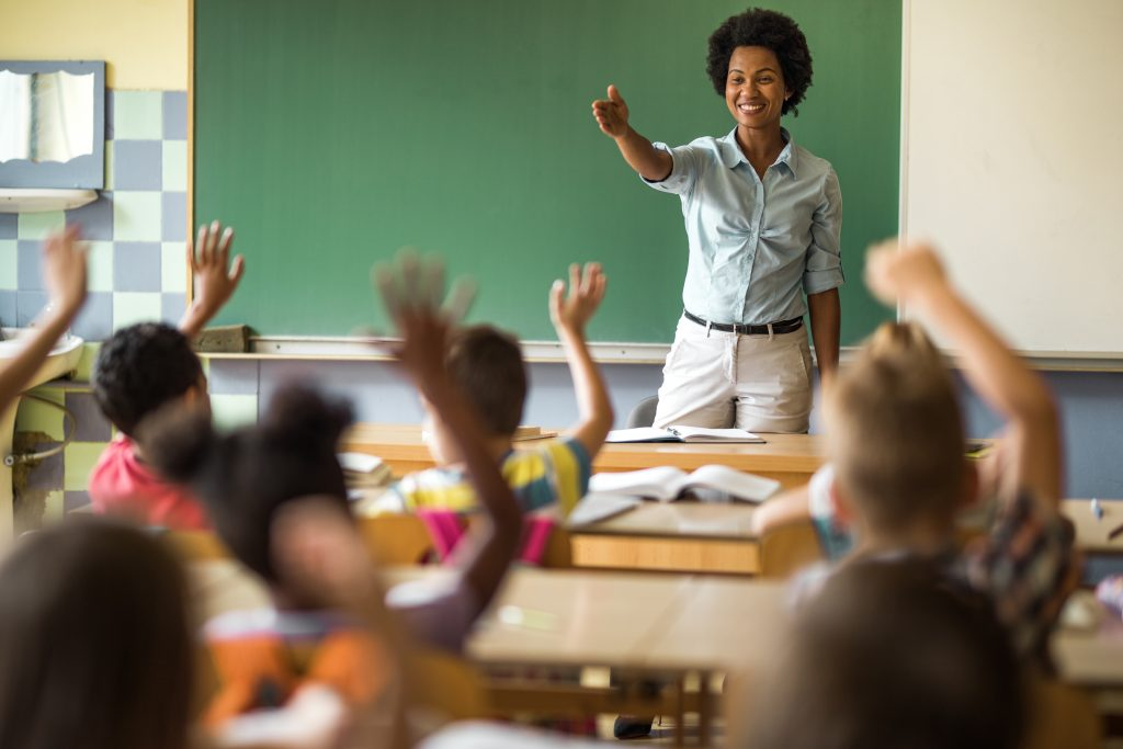 Happy black teacher pointing at a school child to answer her question on a class at elementary school.